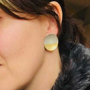 Electra Stud Earrings in Silver and Gold by Kokkino, worn by woman with dark hair