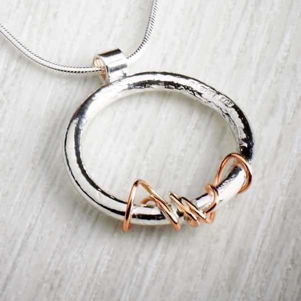 Ivy Twist Circle pendant, silver & gold details by Sally Ratcliffe, image property of THE JEWELLERY MAKERS