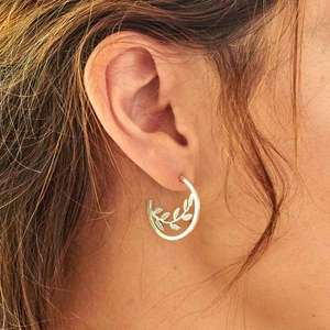 Mismatched silver hoops, with a bird and leaves by Helen Shere, worn on, leaves