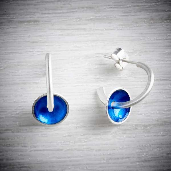 Modern silver hoops with blue enamel discs on grey background by Kokkino