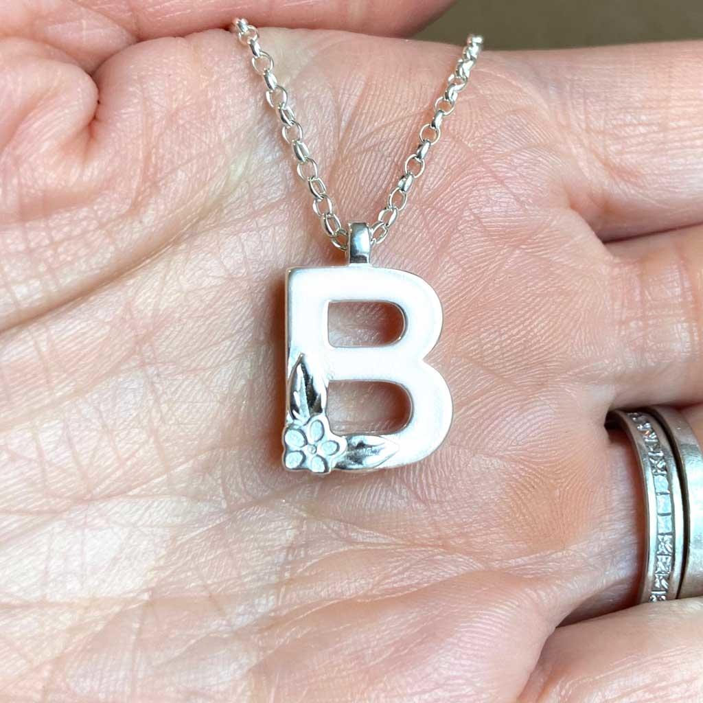 Silver Letter Necklace - B by Elin Mair, Image property of THE JEWELLERY MAKERS in hand