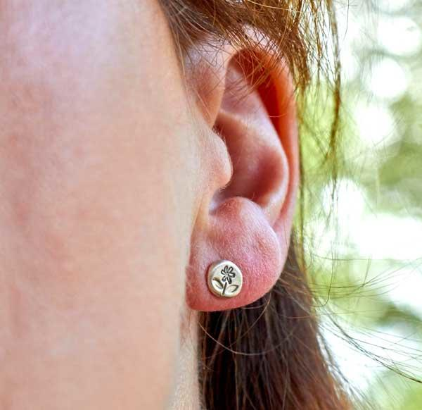 Tiny Silver Flower Stud earrings by Helen Shere, worn by model