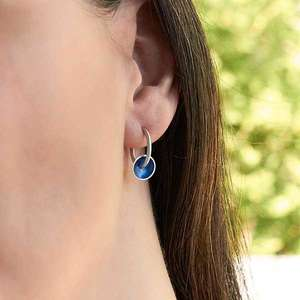 Modern silver hoops with blue enamel discs worn on by Kokkino
