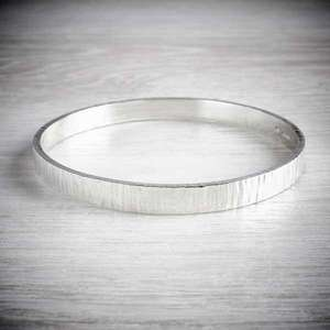 Wide Hammered Silver Bangle with Emma White. Image property of THE JEWELLERY MAKERS