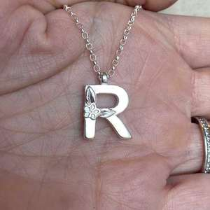 Silver Letter R Necklace, made by Elin Mair, Image property of THE JEWELLERY MAKERS in hand.