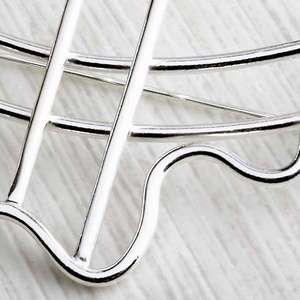Close up of handmade silver brooch, abstract wiggle with sweeping lines by Alice Chandler