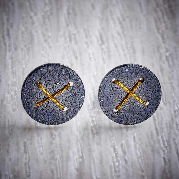 Oxidised Silver Stud Earrings with Gold Cross by Sara Bukumunhe. Image property of THE JEWELLERY MAKERS.