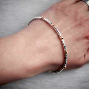 Contemporary handmade silver bangle with rose gold nuggets