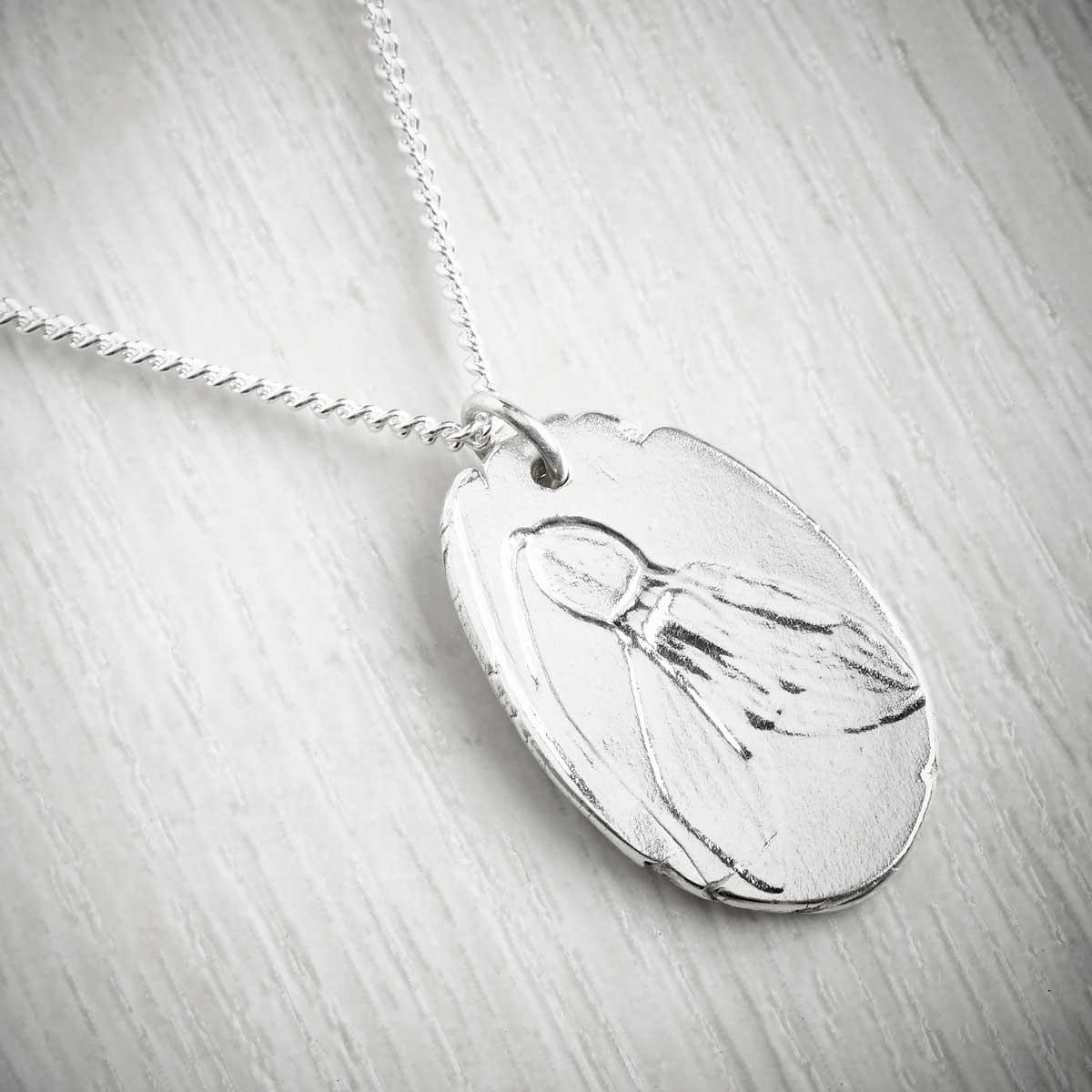 Handmade necklace with a snowdrop imprint on a grey background. Made by Becca Macdonald, image property of THE JEWELLERY MAKERS.