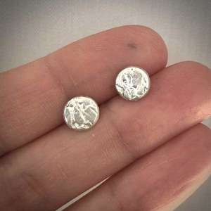 Silver Creased Studs by Becca Macdonald held in hand