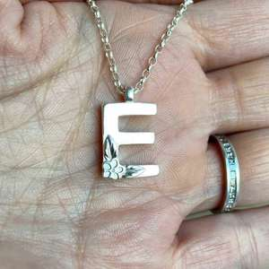 Silver Initial necklace, Letter E. Made by Elin Mair, image property of THE JEWELLERY MAKERS in hand