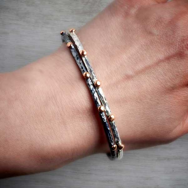Contemporary handmade silver bangle with rose gold nuggets and oxidised silver bangle with gold nuggets worn together on wrist