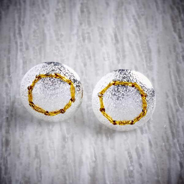 Handmade silver stud earrings sewn up with a circle of gold thread