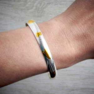 Handmade silver and gold Keum Boo bangle by Fi Mehra, worn on an arm