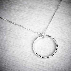 Silver personalised circle necklace with tiny stamped letters, close up