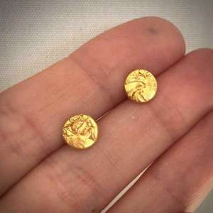 Gold handmade stud earrings with creased texture by Becca Macdonald for THE JEWELLERY MAKERS in the hand