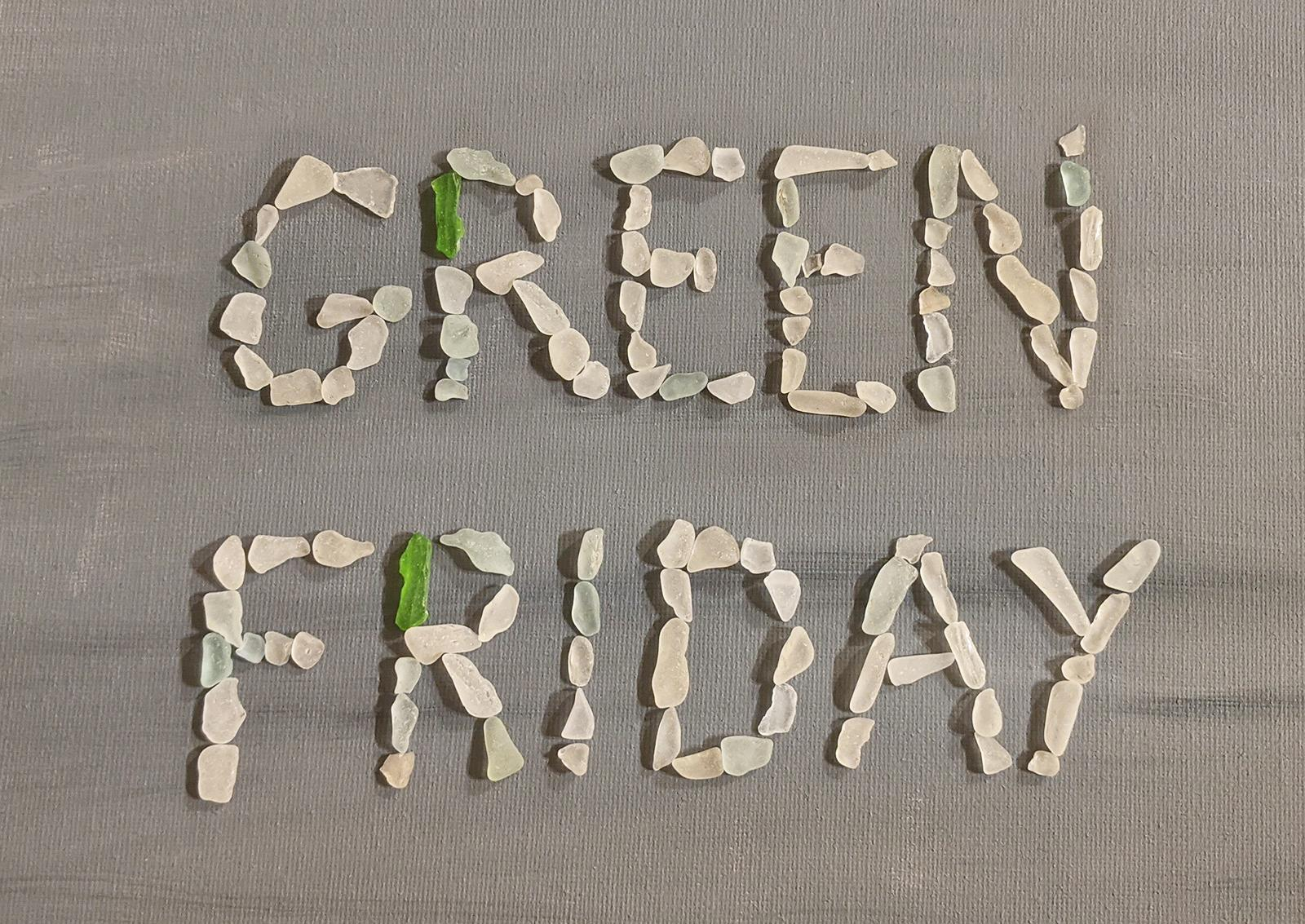 Green Friday written in glass pebbles found on beach