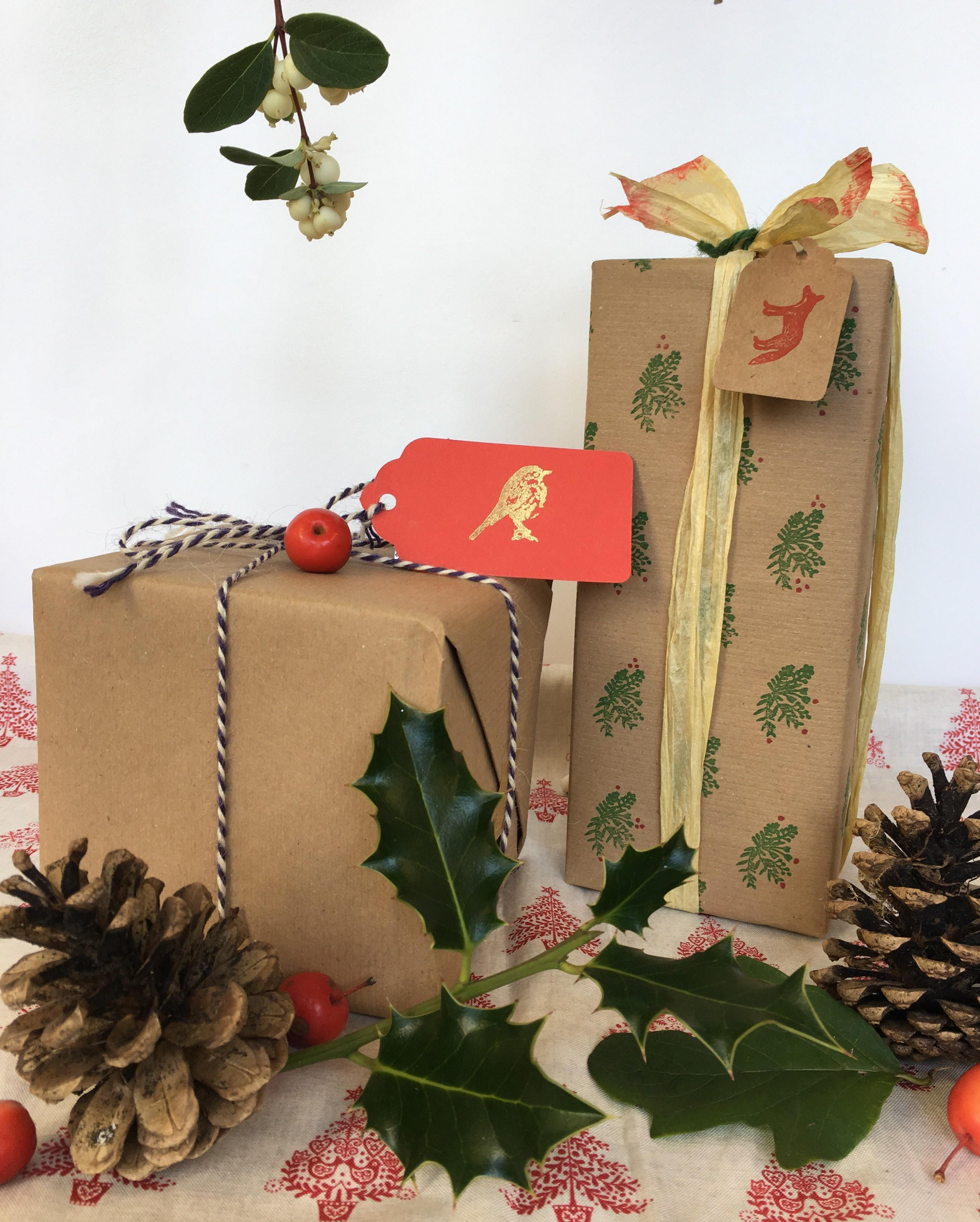 Image shows to boxes wrapped with kraft paper and decorated with string, ribbons and natural items such as holly and pines