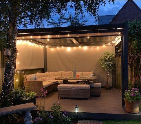 aluminium garden gazebo in grey with night time lights for cosy lounge seating