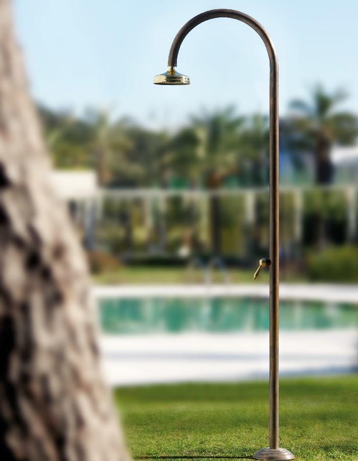 copper outdoor shower in antique copper and brass  by swimming pool in garden
