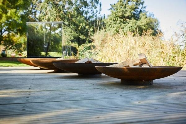 row of corten steel modern garden fire bowls