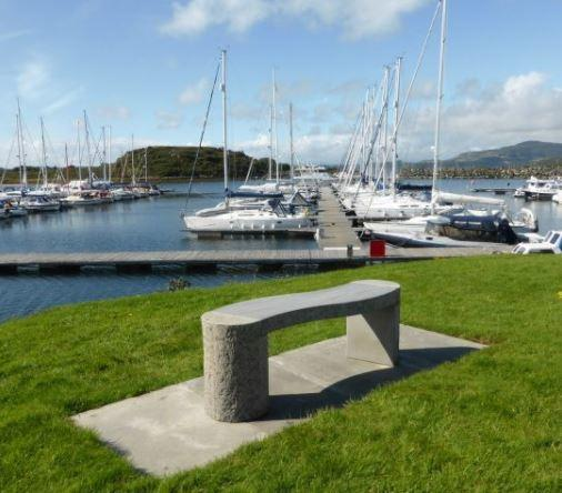 grey sandstone garden bench in outdoor marina setting