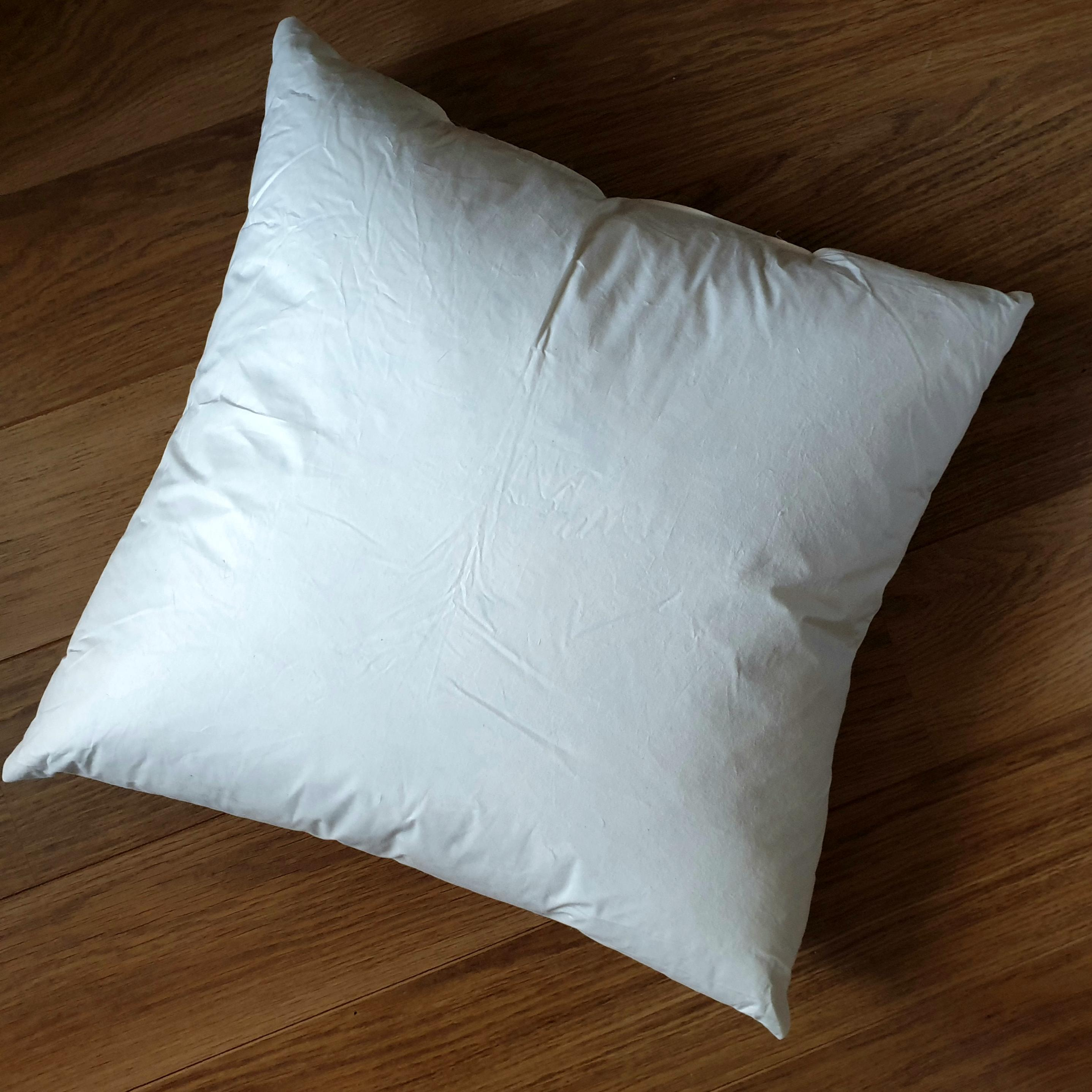 55cm cushion inner pad generously filled with 100% white duck feathers in ecru cream 100% cotton outer cover.