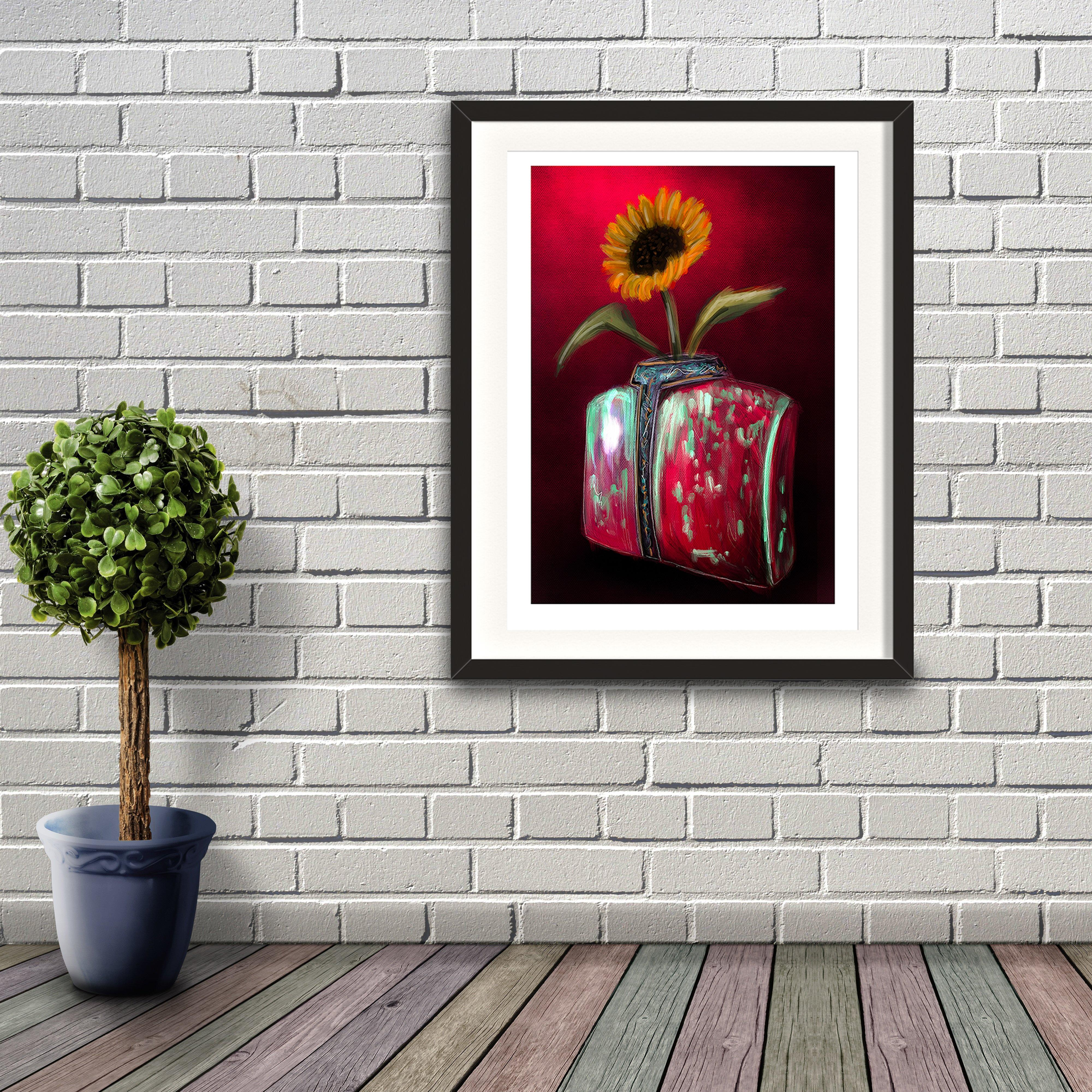 A digital painting by Lily Bourne printed on eco fine art paper titled Blooming showing a solitary sunflower in a torso shaped red and green coloured against a deep red wall. Artwork shown framed against a brick wall.