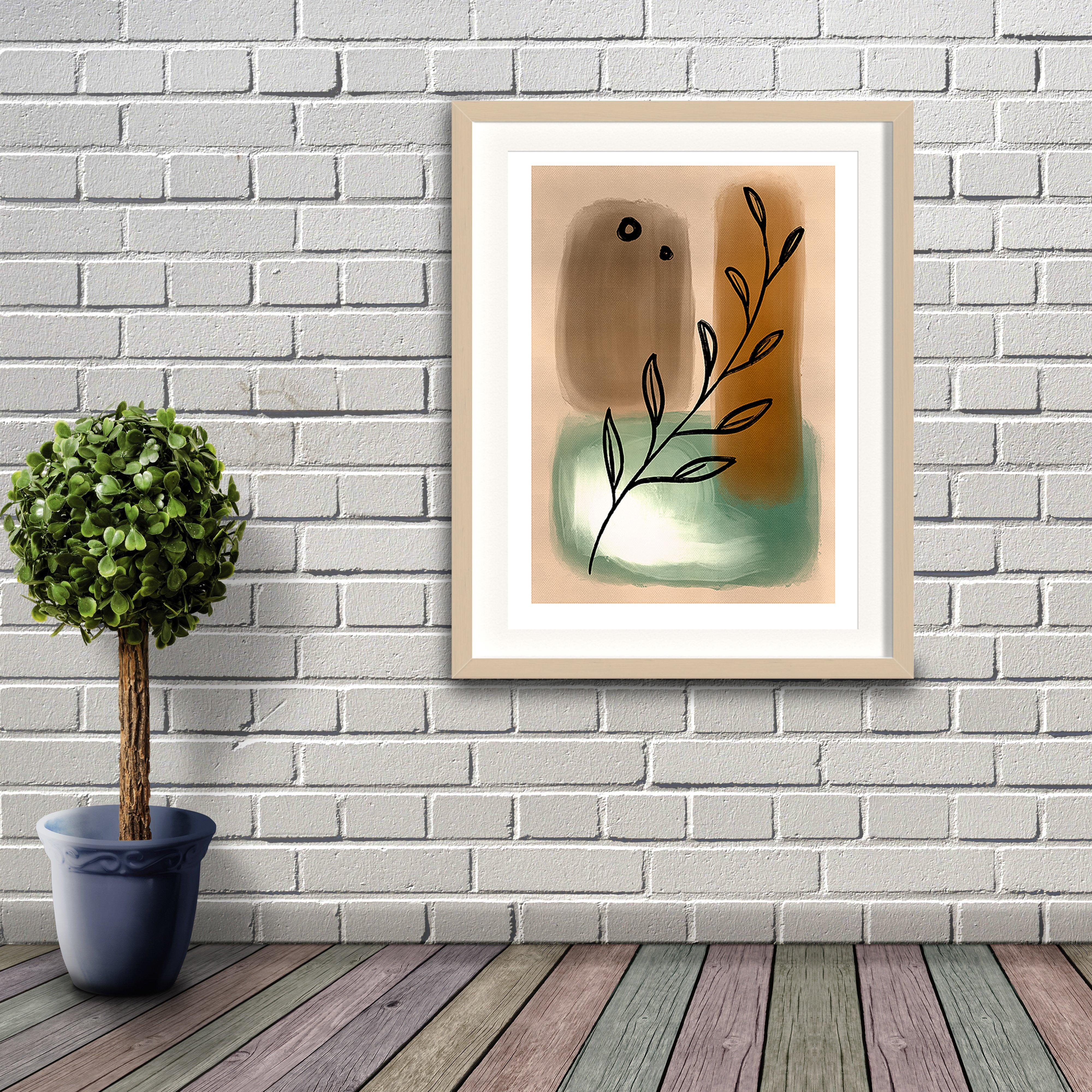 An abstract digital painting by Lily Bourne printed on eco fine art paper titled Tranquil Moment showing a line drawn olive branch over neutral green and brown painted hues. Artwork is shown in a black frame hanging on a brick wall.