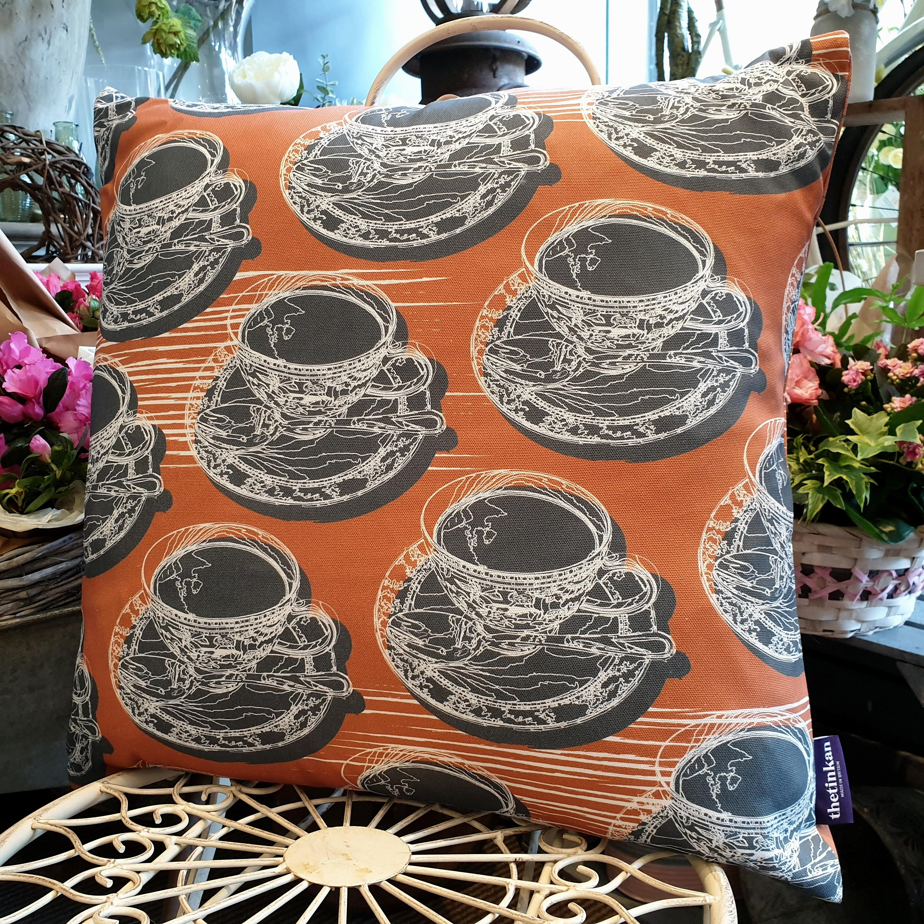 Double-sided warm rust orange 51cm square retro Afternoon Tea cushion with artistic white shards designed by thetinkan. White traced outline of multiple British teacups and saucers each colour filled in charcoal grey. Available with an optional luxury cushion inner pad. VIEW PRODUCT >>