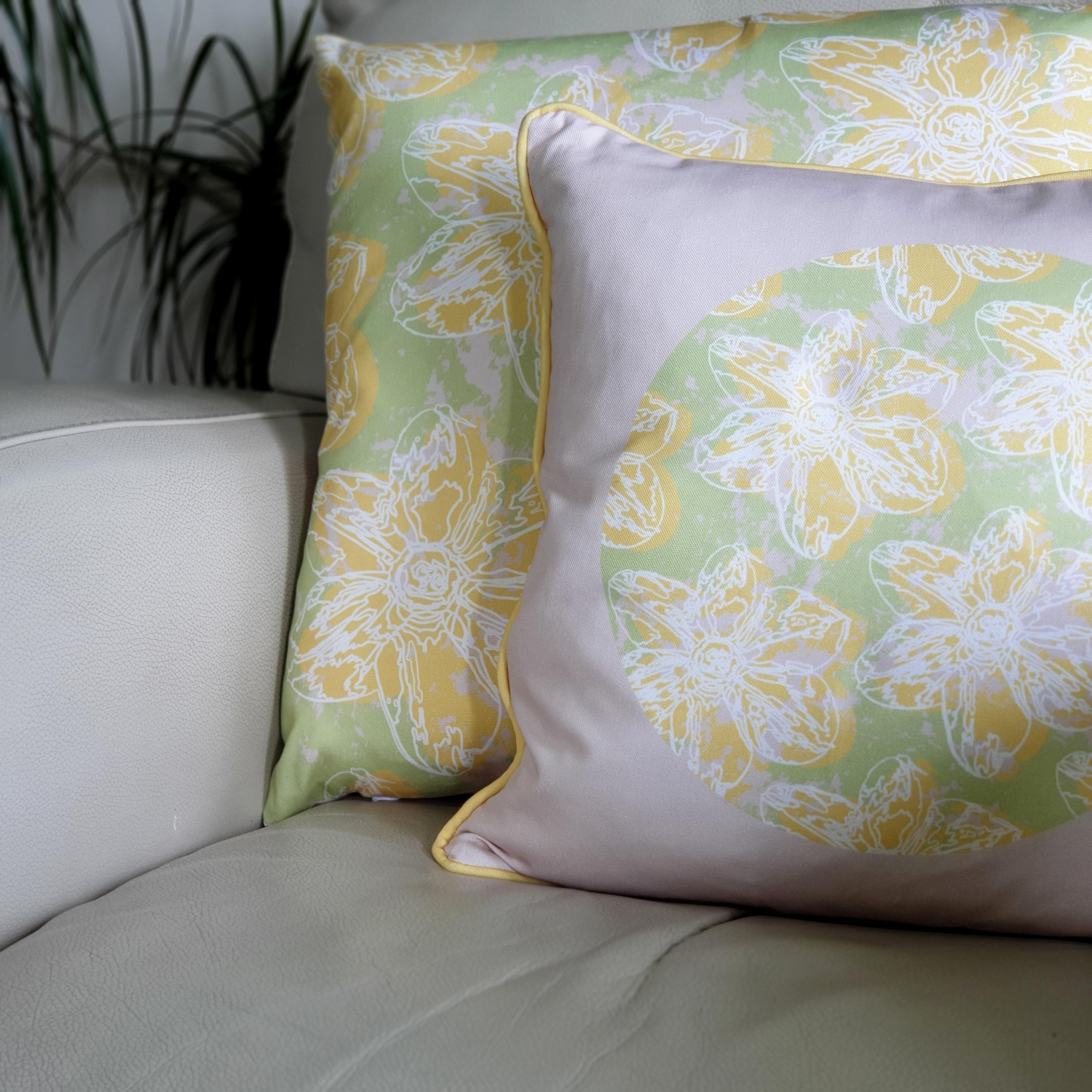 Double-sided 45cm square & 51cm square Flower Splash cushions, showing both sides, designed by thetinkan. Yellow narcissus flower with white traced outline set within a mint green background with pale pink paint splashes. Available with an optional luxury cushion inner pad. VIEW PRODUCT >>