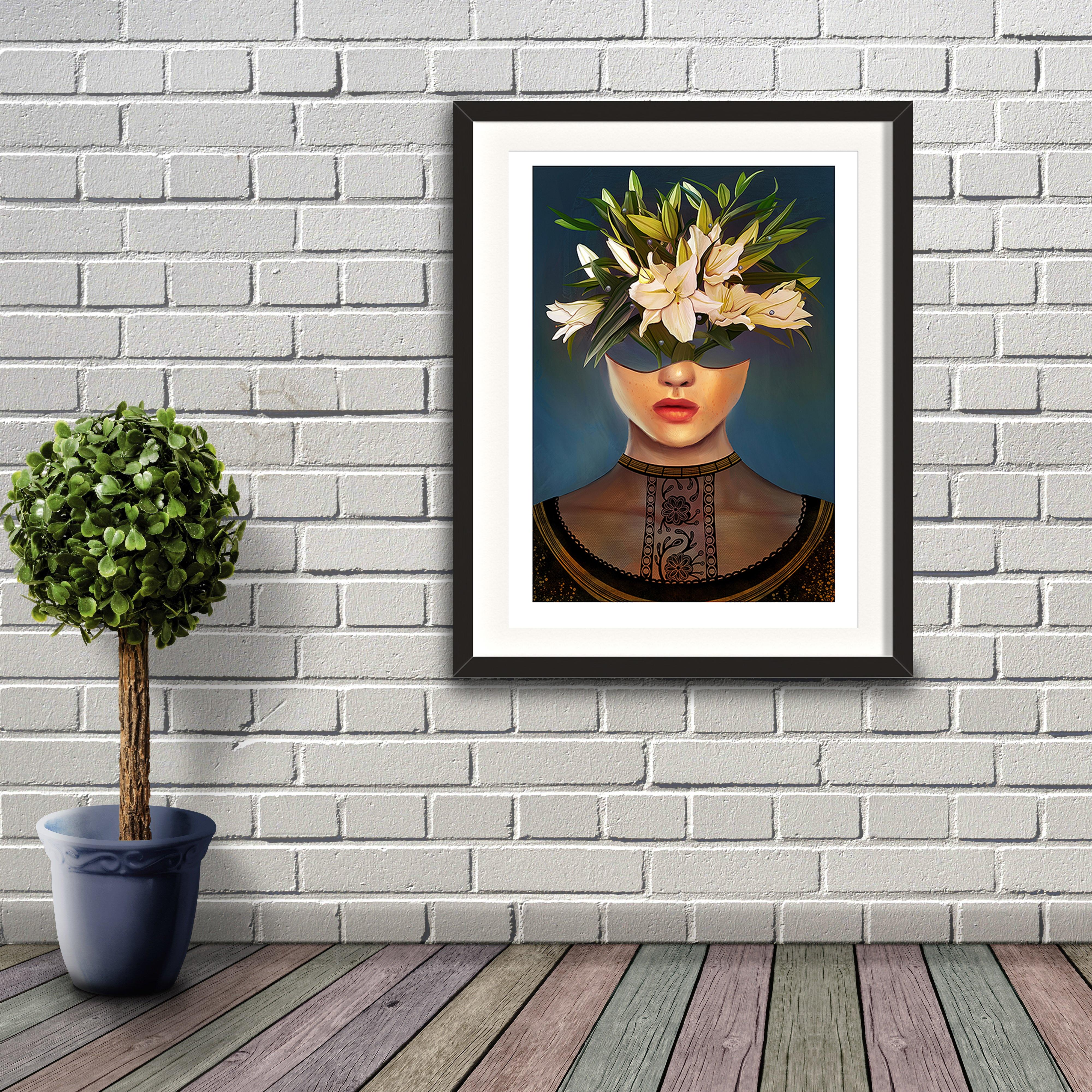 A digital painting by Lily Bourne printed on eco fine art paper titled Lilium showing a female head dressed in a black lace top. The head acts as a vase for white lily flowers. Artwork shown in a black frame hanging on a brick wall.