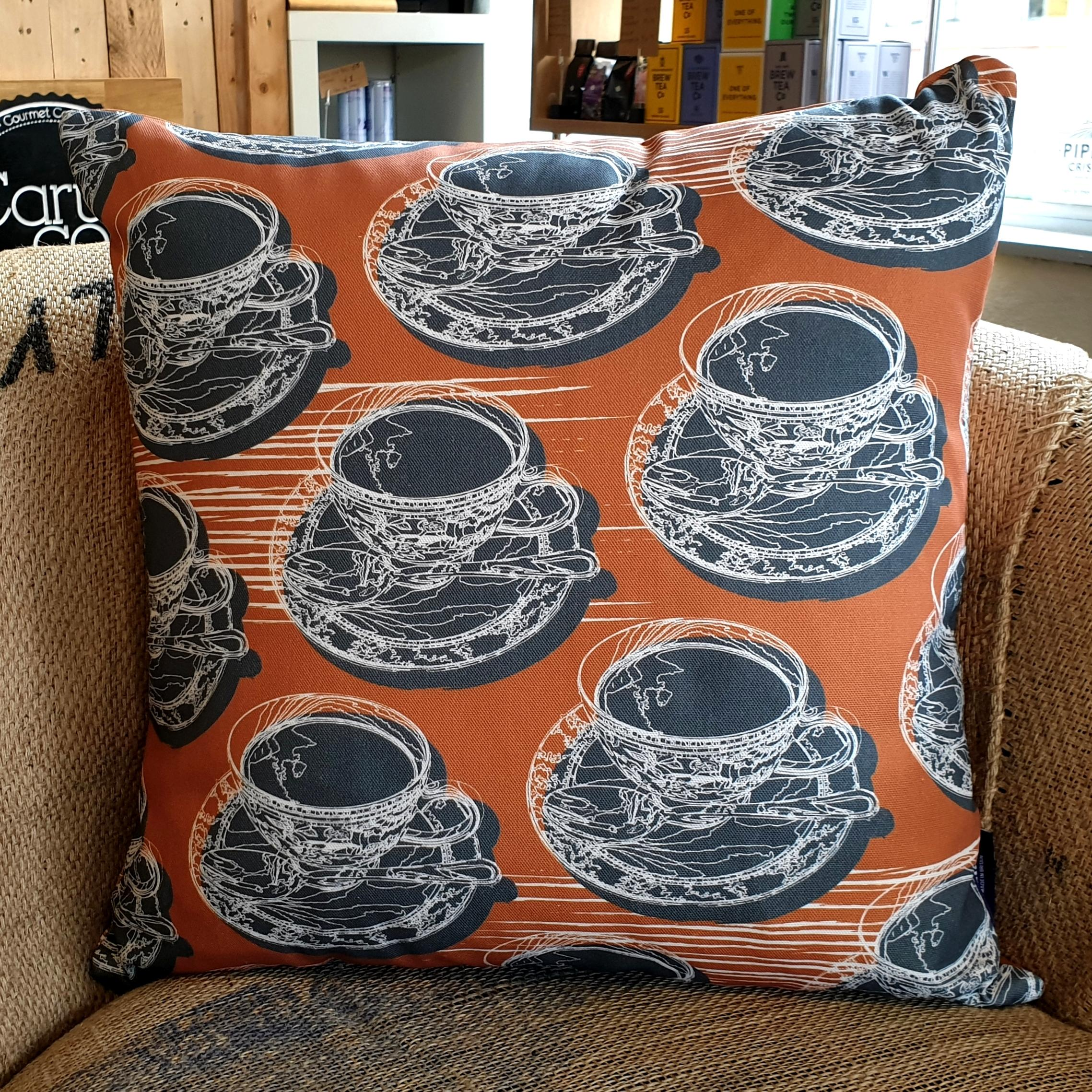 Double-sided warm rust orange 45cm square retro Afternoon Tea cushion with artistic white shards designed by thetinkan. White traced outline of multiple British teacups and saucers each colour filled in charcoal grey. Available with an optional luxury cushion inner pad. VIEW PRODUCT >>
