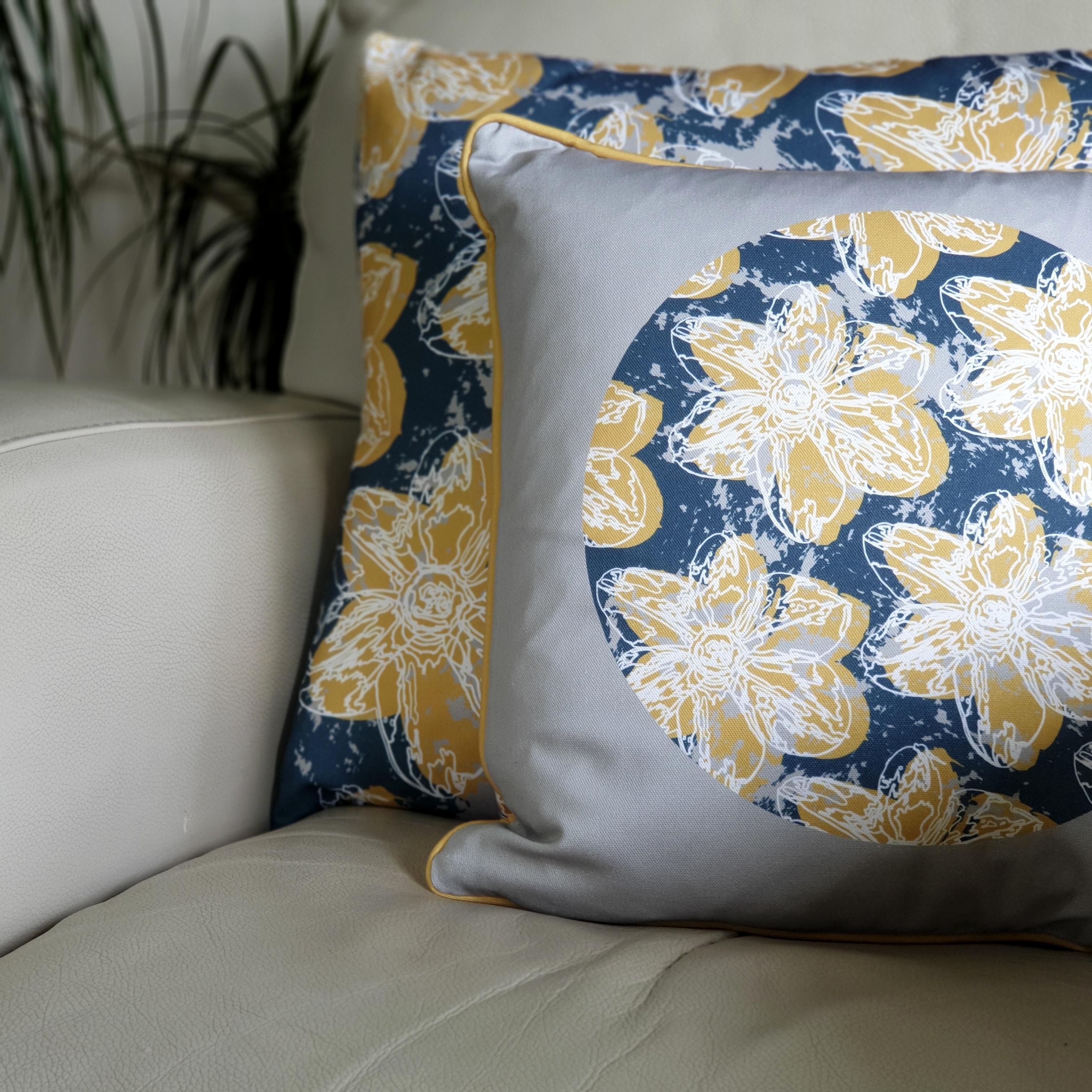 Double-sided 45cm square & 51cm square Flower Splash cushions, showing both sides, designed by thetinkan. Mustard yellow narcissus flower with white traced outline set within an oxford blue background with pale grey paint splashes. Available with an optional luxury cushion inner pad. VIEW PRODUCT >>