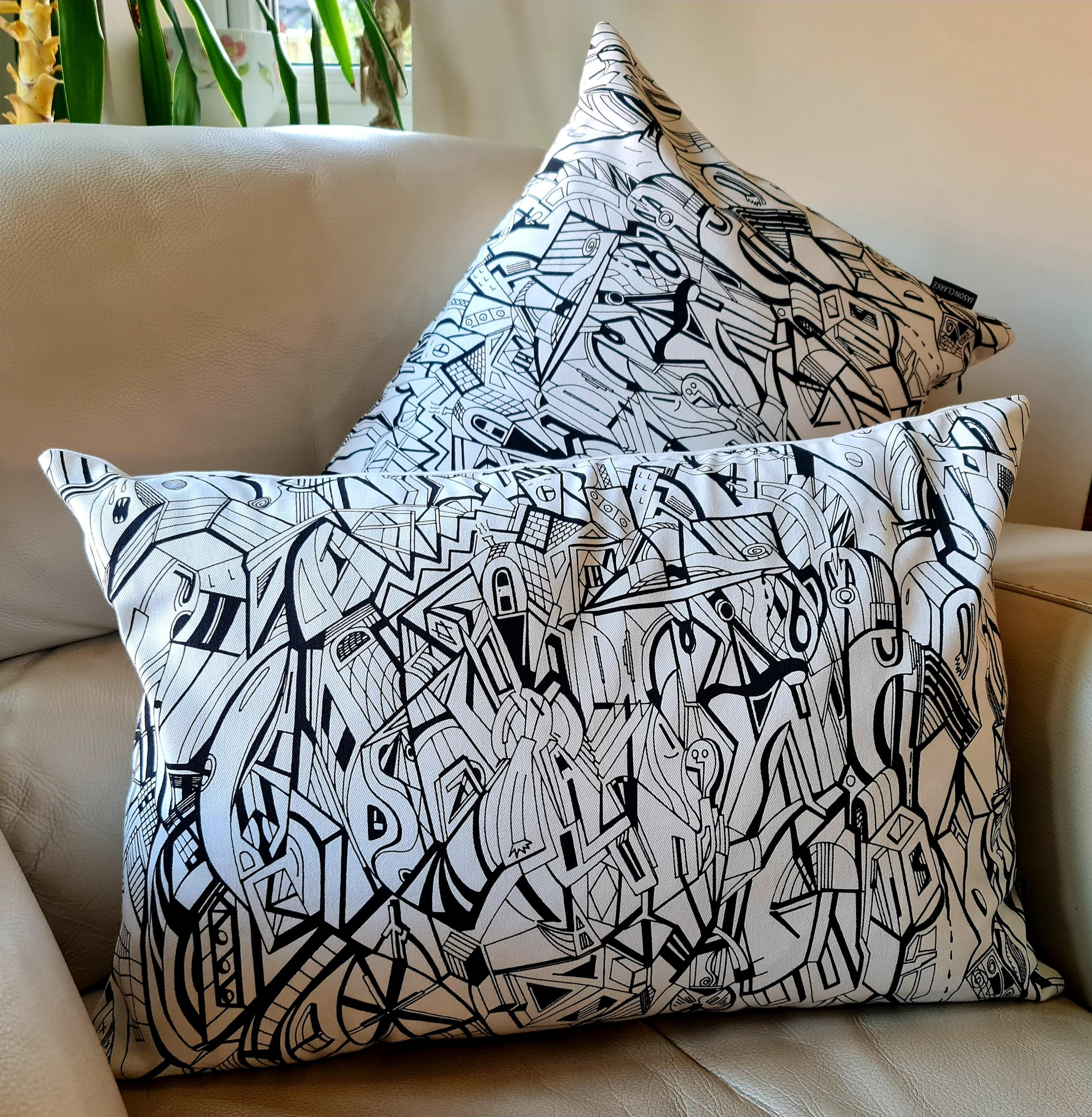 Cream coloured cotton rectangular cushion with artwork from Jason Clarke printed on the front.