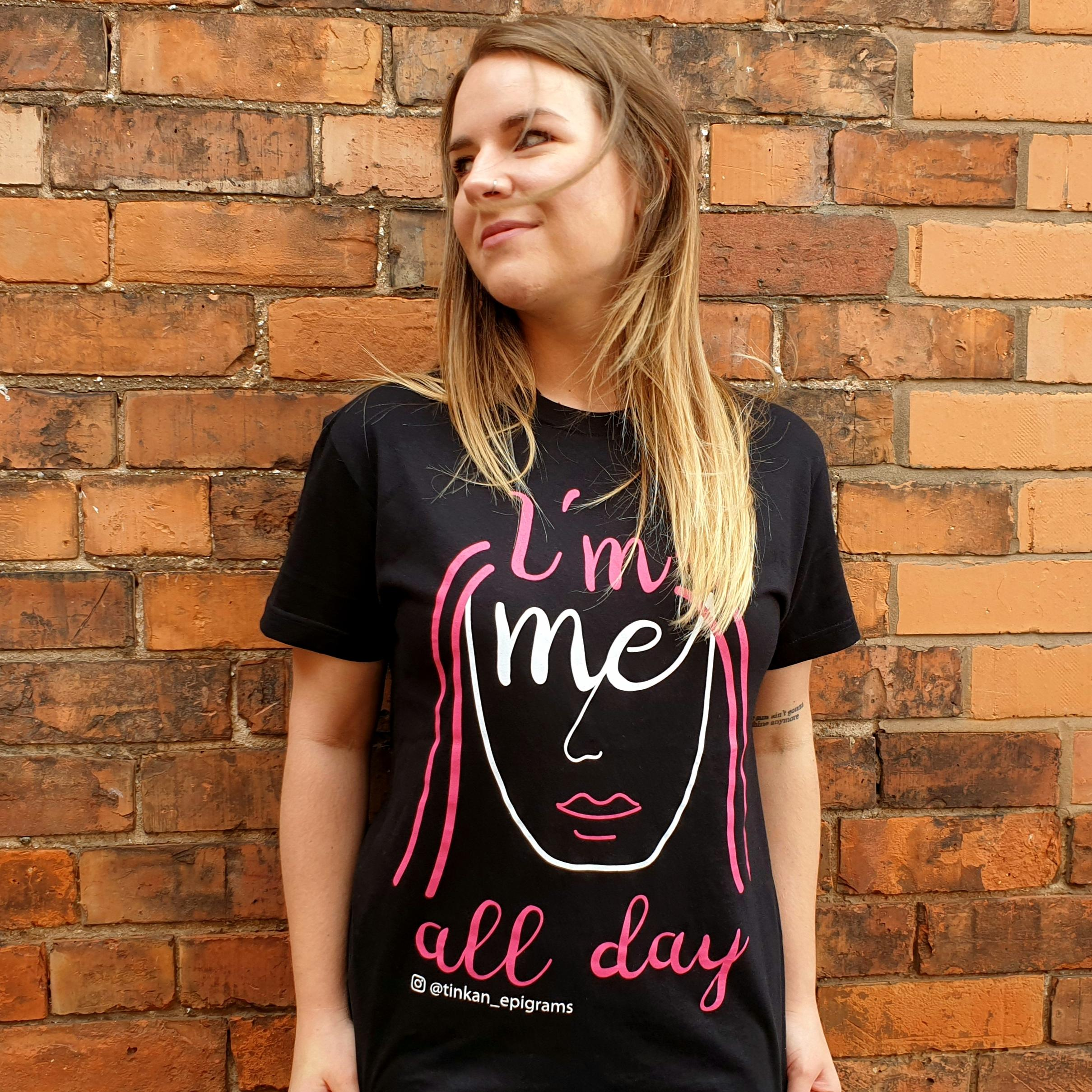 Adult female wearing black t-shirt with white handdrawn face with pink hair with the words I'm Me All Day printed. Designed by thetinkan. VIEW PRODUCT >>