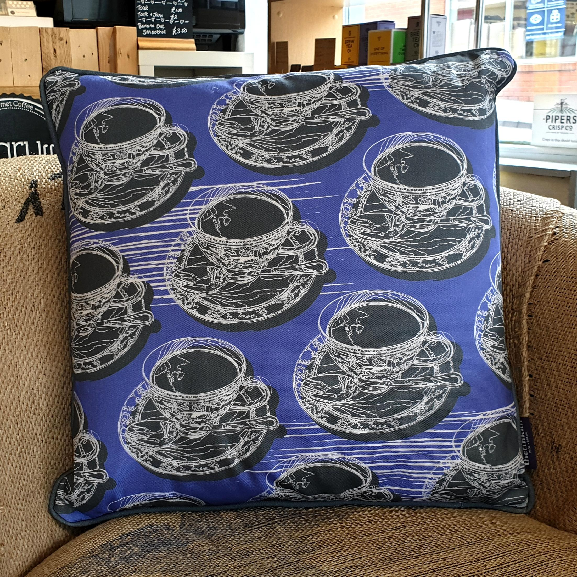 Double-sided violet purple 45cm square retro Afternoon Tea cushion with artistic white shards and grey handcrafted piping designed by thetinkan. White traced outline of multiple British teacups and saucers each colour filled in charcoal grey. Available with an optional luxury cushion inner pad. VIEW PRODUCT >>