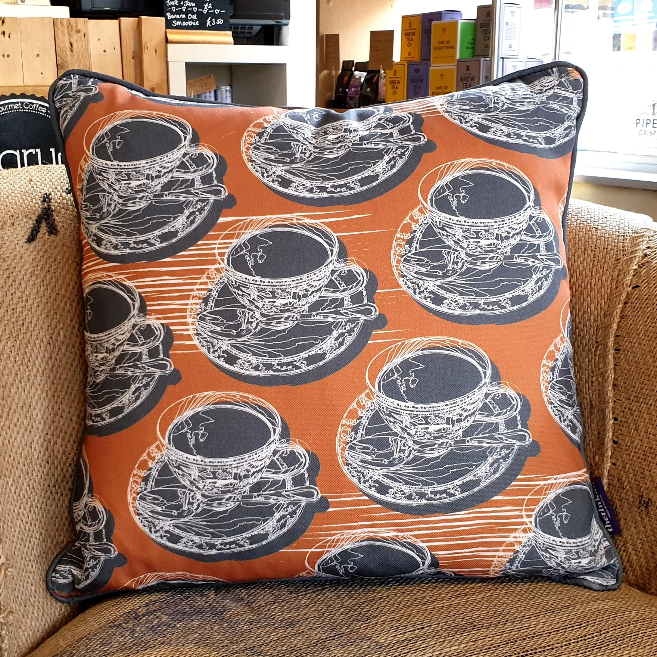 Double-sided warm rust orange 45cm square retro Afternoon Tea cushion with artistic white shards and grey handcrafted piping designed by thetinkan. White traced outline of multiple British teacups and saucers each colour filled in charcoal grey. Available with an optional luxury cushion inner pad. VIEW PRODUCT >>