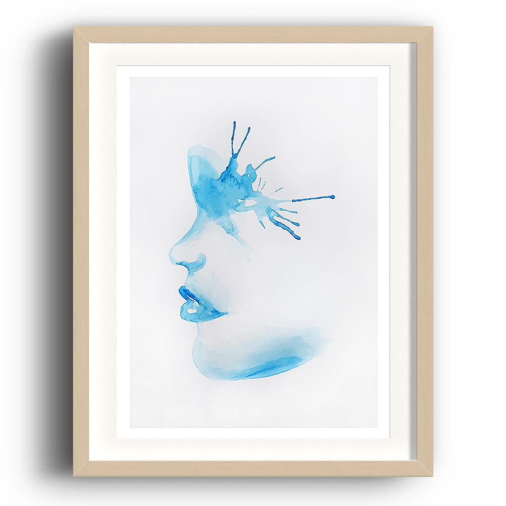 A watercolour print by Clarrie-Anne on eco fine art paper titled A Splash Of The Blues show a blue watercoloue side profile of a female face with a paint splash around the eye. The image is set in a beech coloured picture frame.