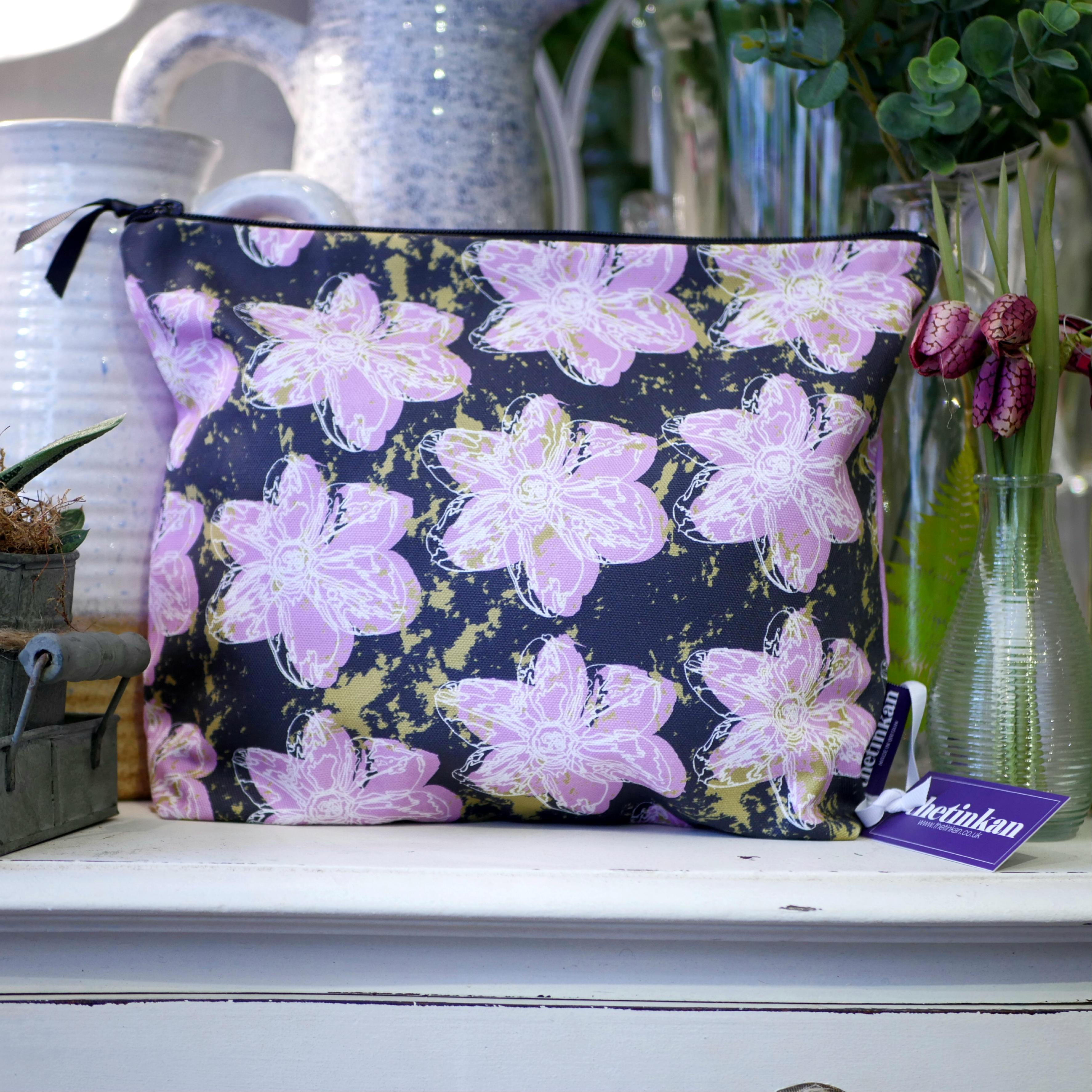 Candy pink flower with a matching coloured reverse, set on a dark charcoal grey background with an olive green colour splash. Designed by thetinkan, the flower splash travel beauty washbag featuring the white traced outline of a?narcissus flower is made from panama cotton with black waterproof lining and matching black sturdy zip. Generously sized for all your travel or home needs.? VIEW PRODUCT >>