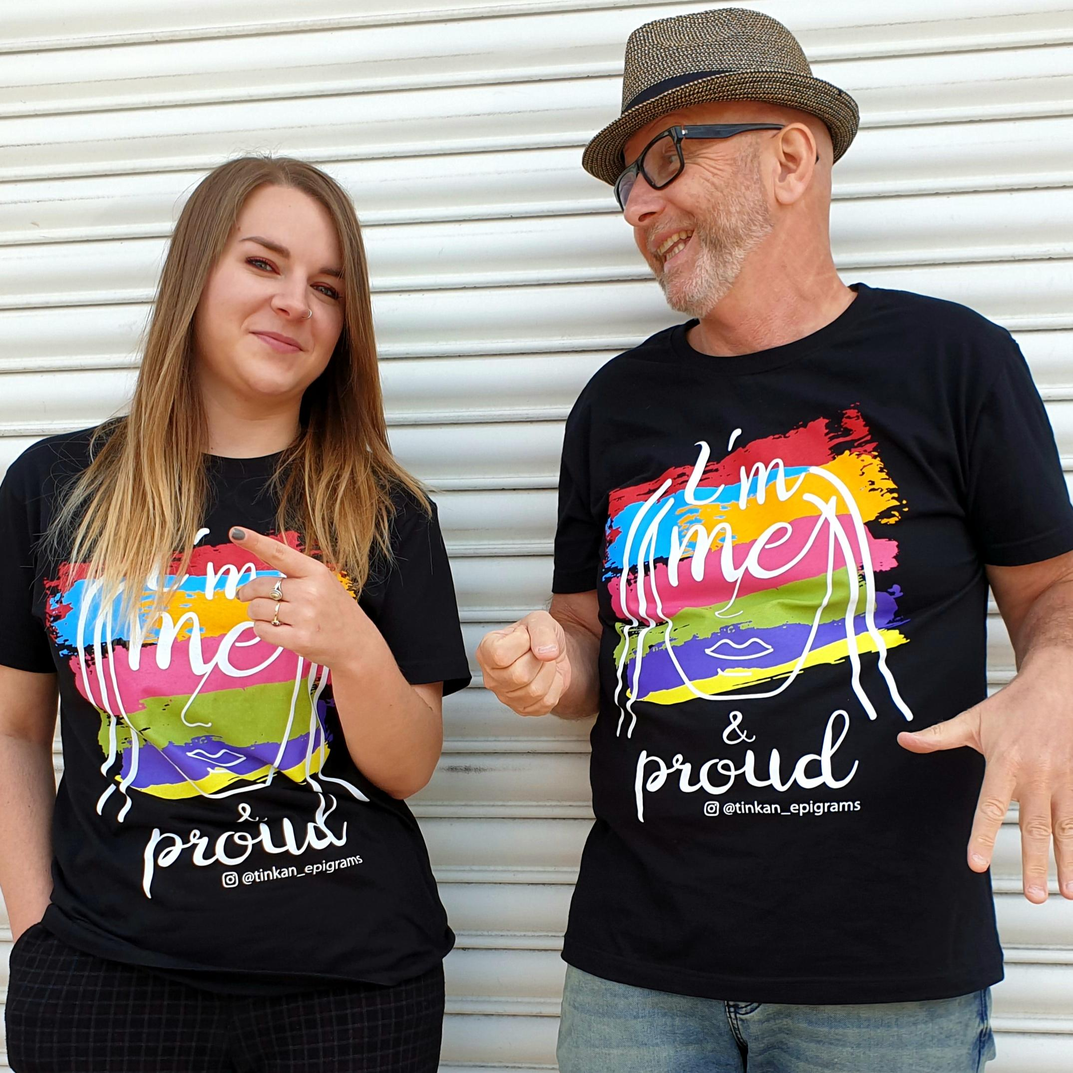 Adult female and male wearing black t-shirt with white handdrawn face and rainbow painted stripes with the words I'm Me & Proud printed. Designed by thetinkan. VIEW PRODUCT >>
