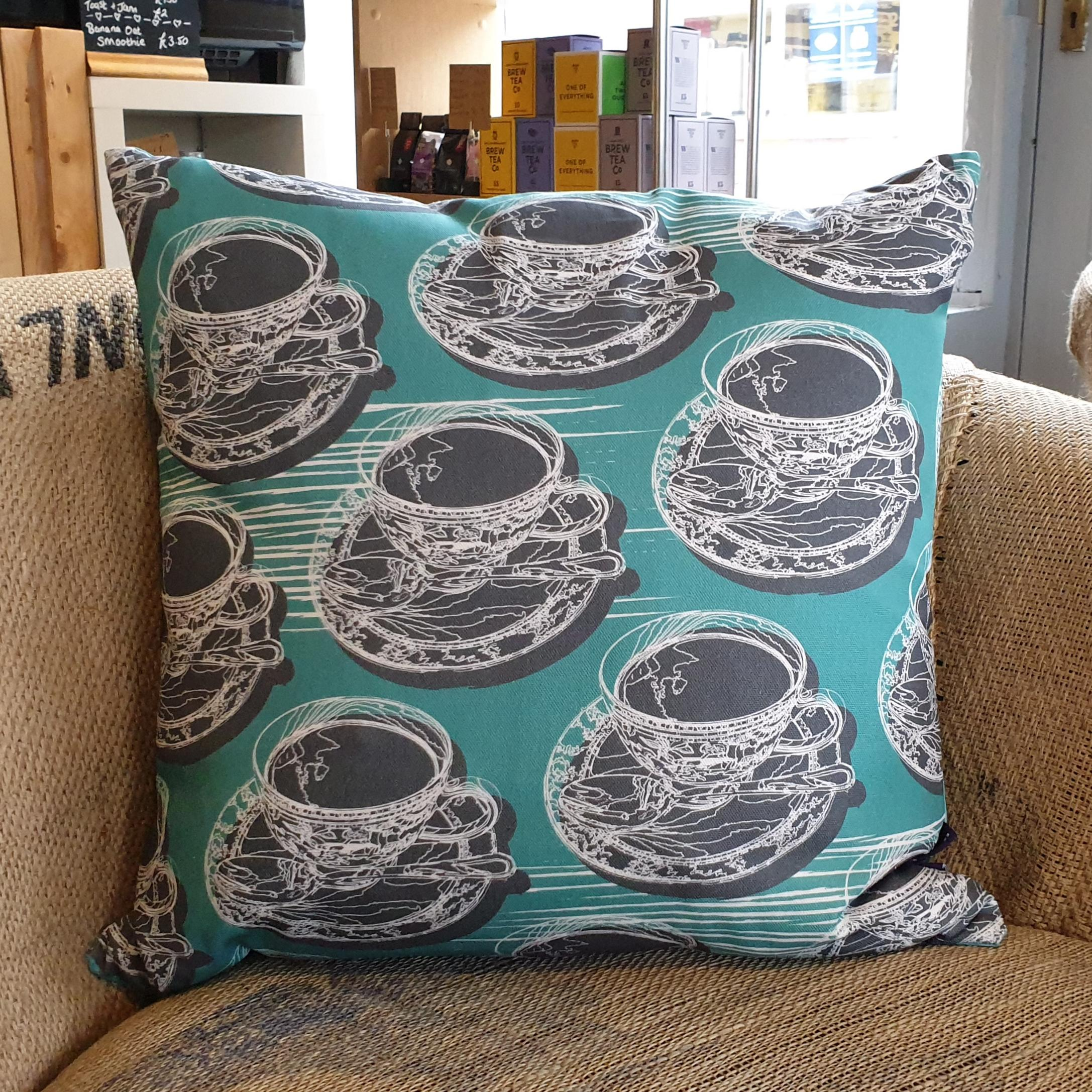 Double-sided aqua teal 45cm square retro Afternoon Tea cushion with artistic white shards designed by thetinkan. White traced outline of multiple British teacups and saucers each colour filled in charcoal grey. Available with an optional luxury cushion inner pad. VIEW PRODUCT >>