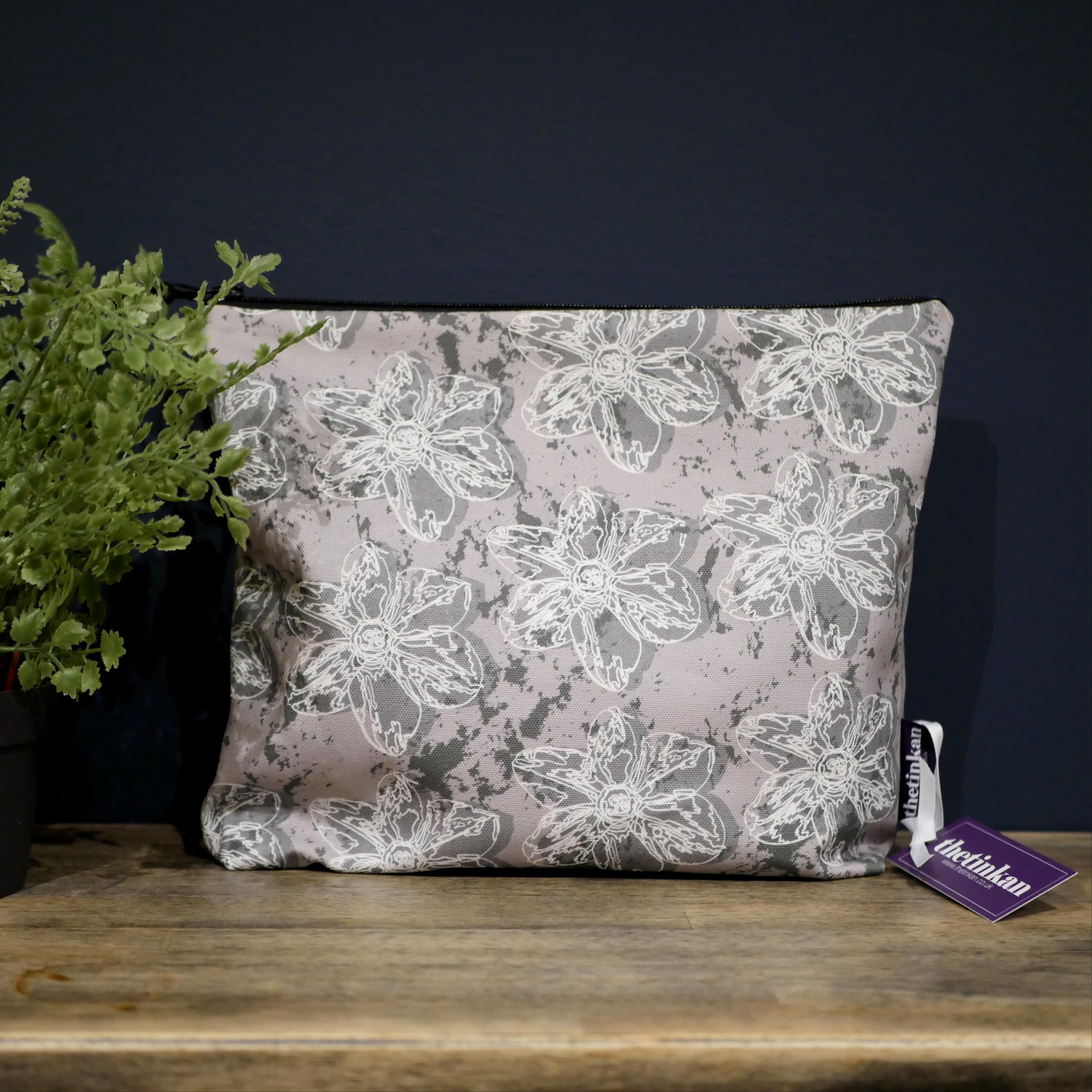 Dark grey flower with a matching coloured reverse, set on an mid grey background with a charcoal grey colour splash. Designed by thetinkan, the flower splash travel beauty washbag featuring the white traced outline of a?narcissus flower is made from panama cotton with black waterproof lining and matching black sturdy zip. Generously sized for all your travel or home needs.? VIEW PRODUCT >>