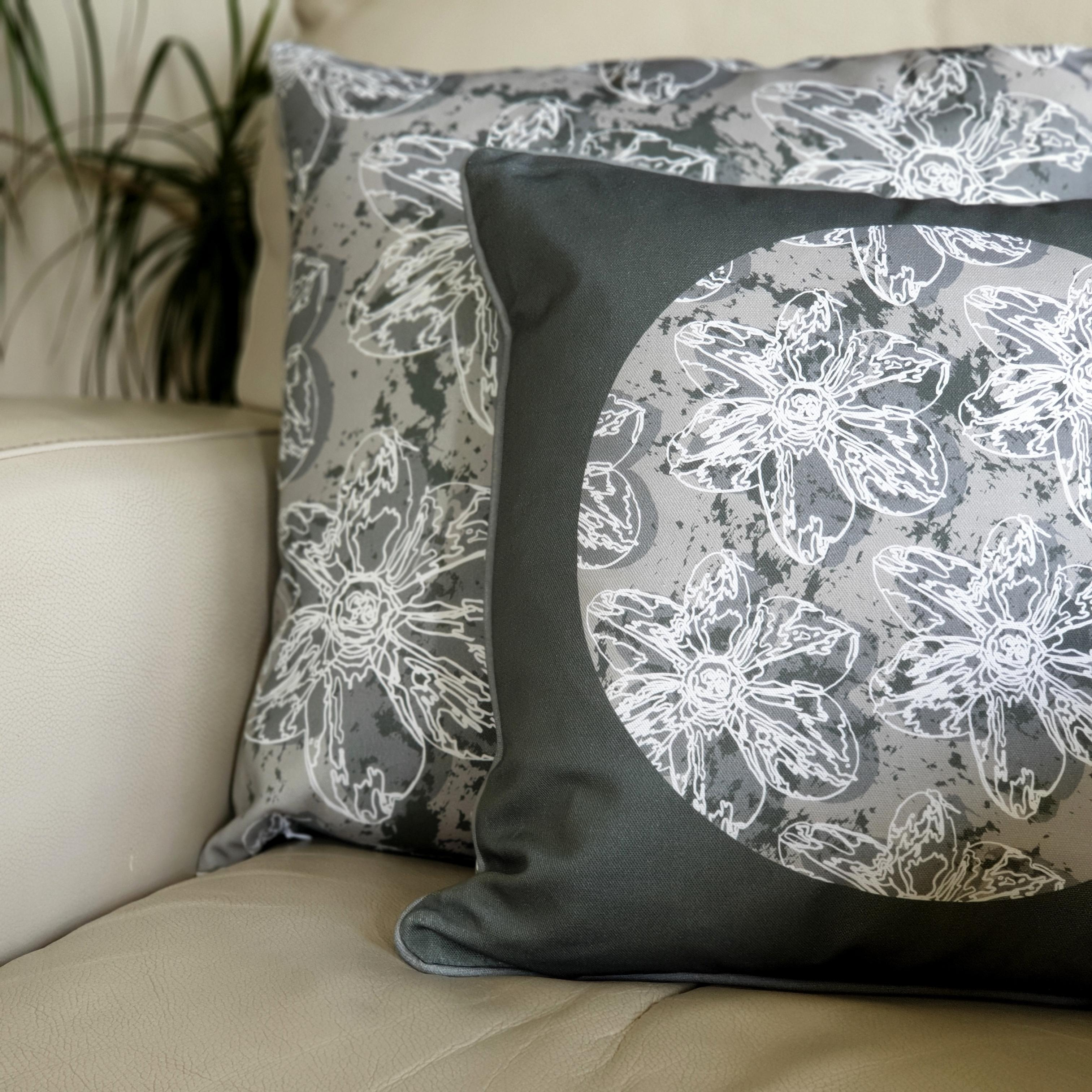 Double-sided 45cm square & 51cm square Flower Splash cushions, showing both sides, designed by thetinkan. Dark grey narcissus flower with white traced outline set within a grey background with charcoal grey paint splashes. Available with an optional luxury cushion inner pad. VIEW PRODUCT >>