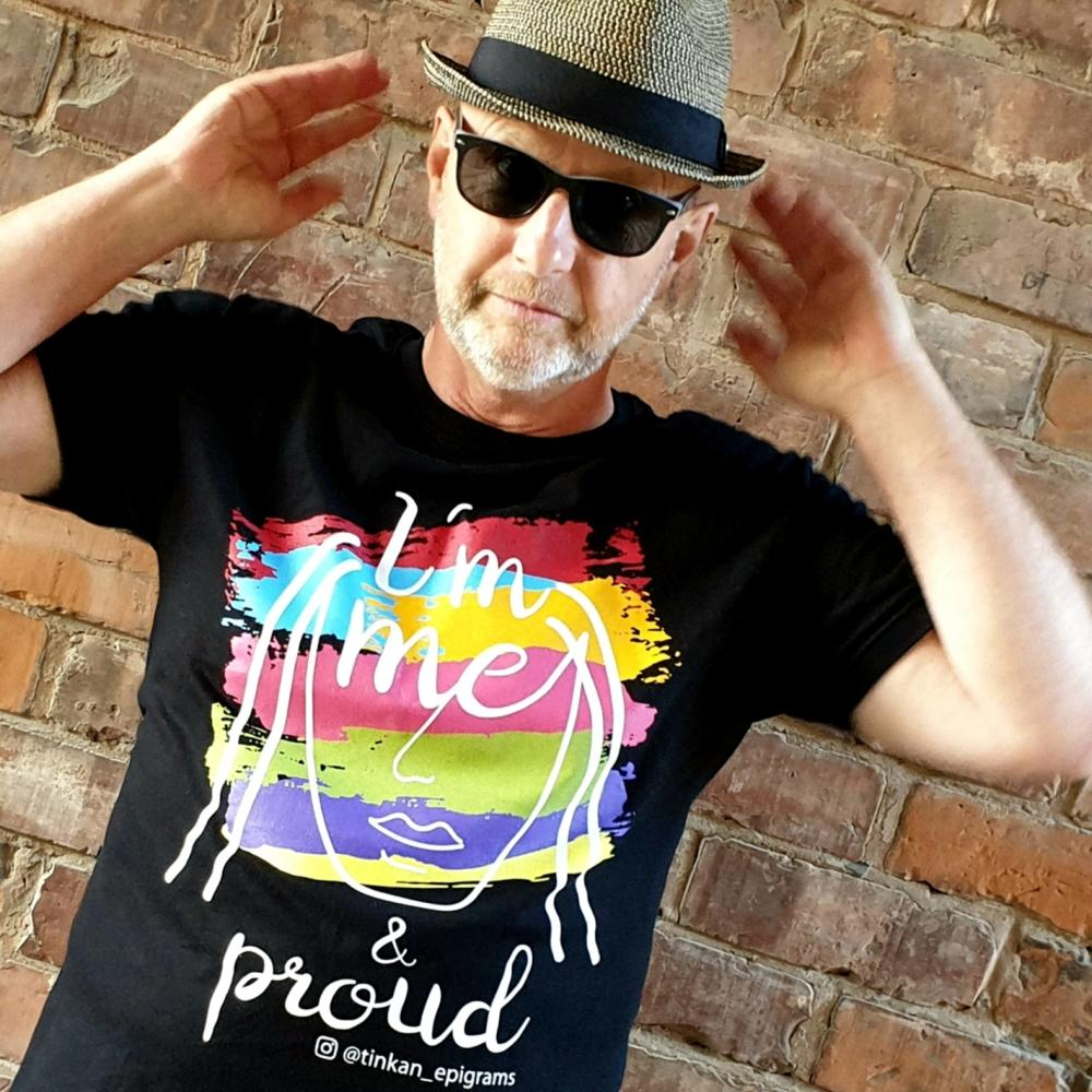 Adult male wearing black t-shirt with white handdrawn face and rainbow painted stripes with the words I'm Me & Proud printed. Designed by thetinkan. VIEW PRODUCT >>