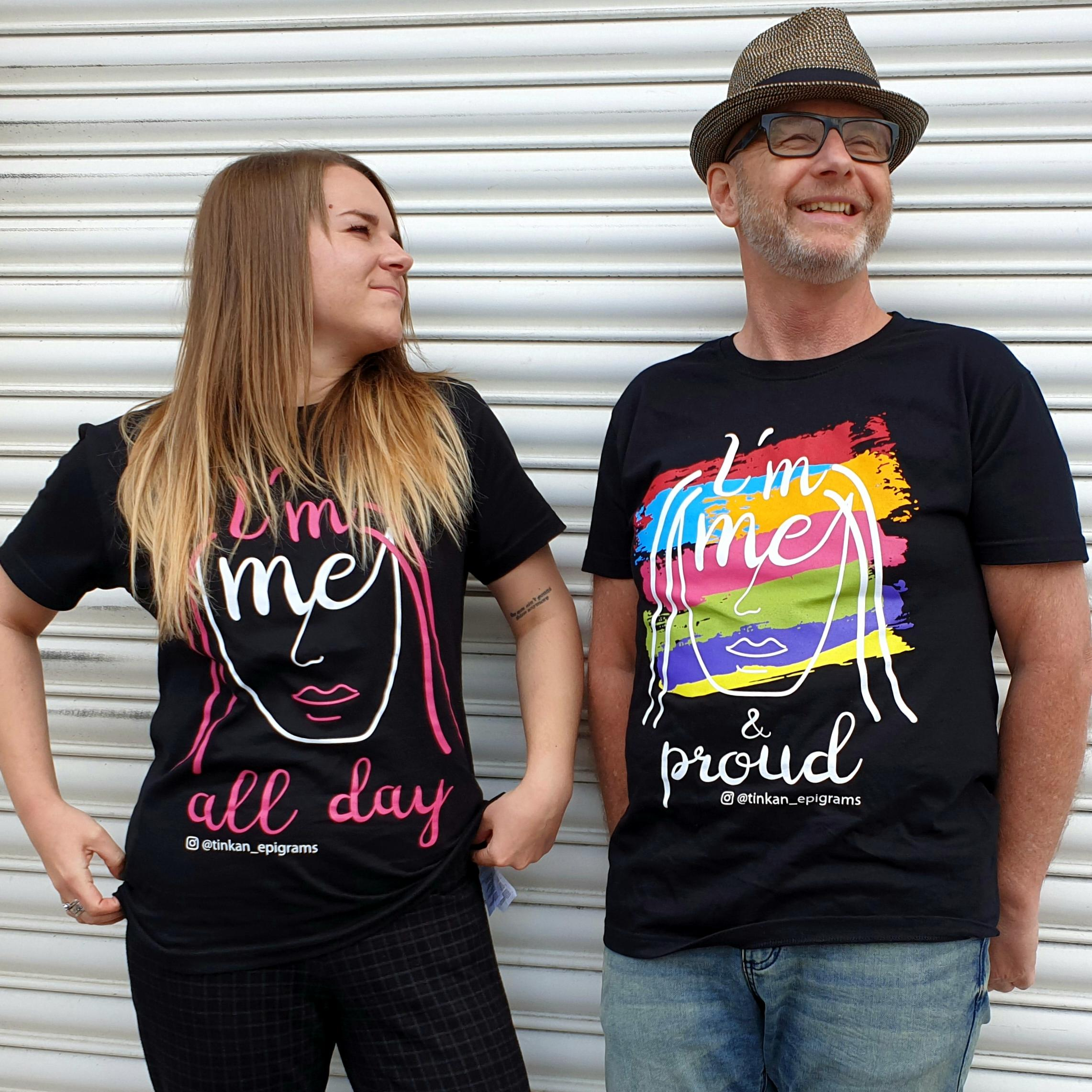 Adult female and male wearing black t-shirt with white handdrawn face with pink hair with the words I'm Me All Day printed and rainbow coloured designed t-shirt with the words I'm Me & Pround printed.. Designed by thetinkan. VIEW PRODUCT >>