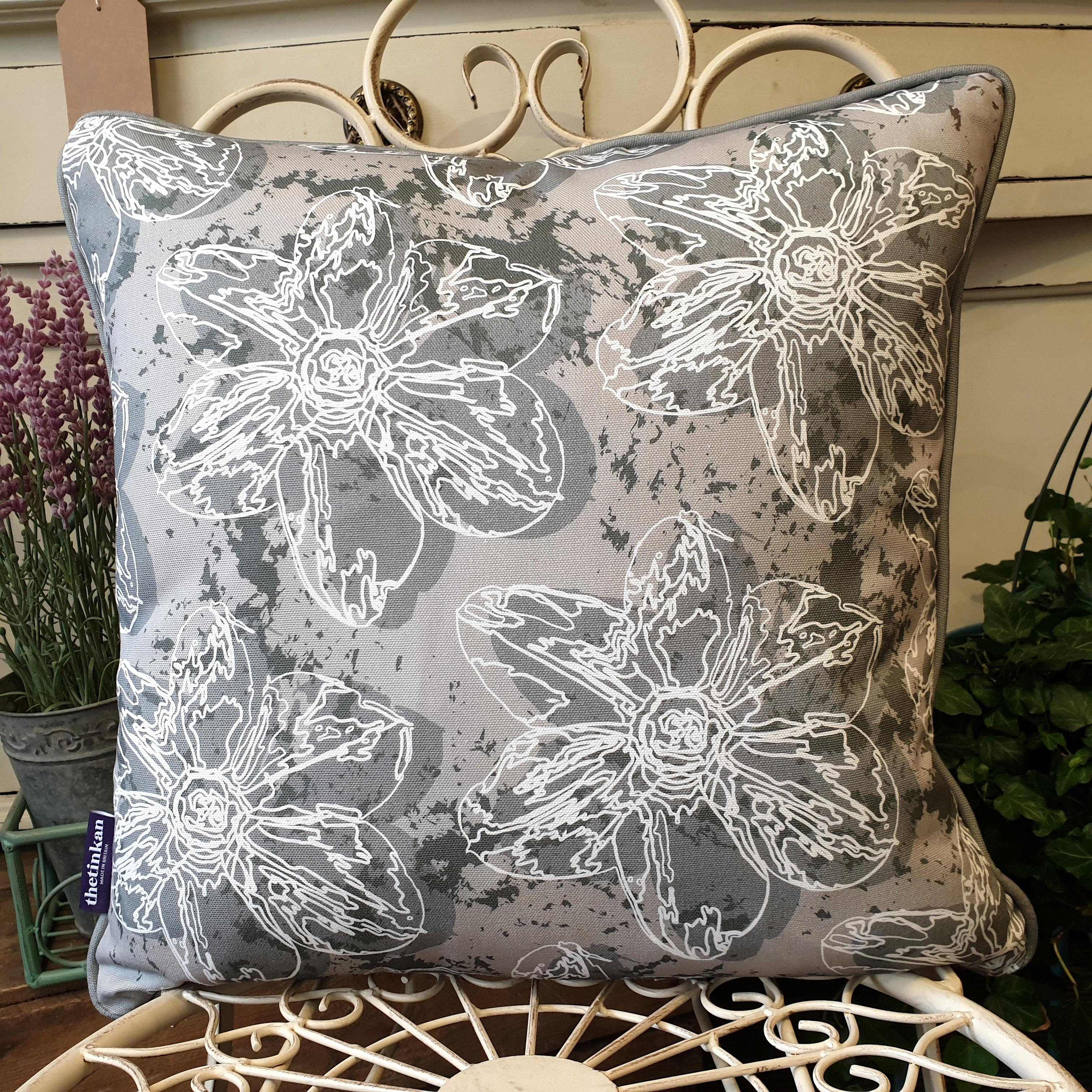 Double-sided 45cm square Flower Splash cushion designed by thetinkan. Dark grey narcissus flower and dark grey piping with white traced outline set within a grey background with charcoal grey paint splashes. Available with an optional luxury cushion inner pad. VIEW PRODUCT >>