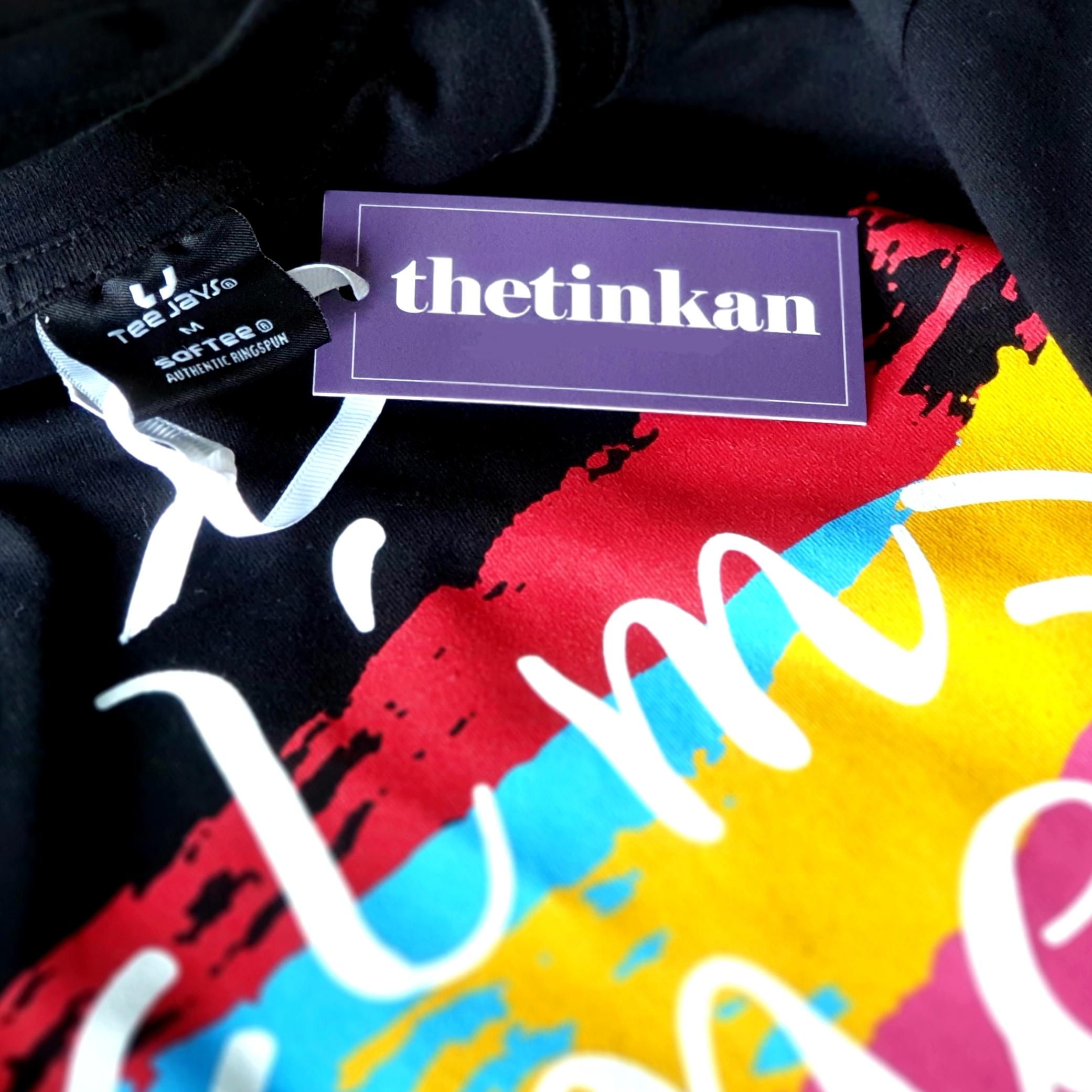 Close up photo of black t-shirt and design tag with white handdrawn face and rainbow painted stripes with the words I'm Me & Proud printed. Designed by thetinkan. VIEW PRODUCT >>
