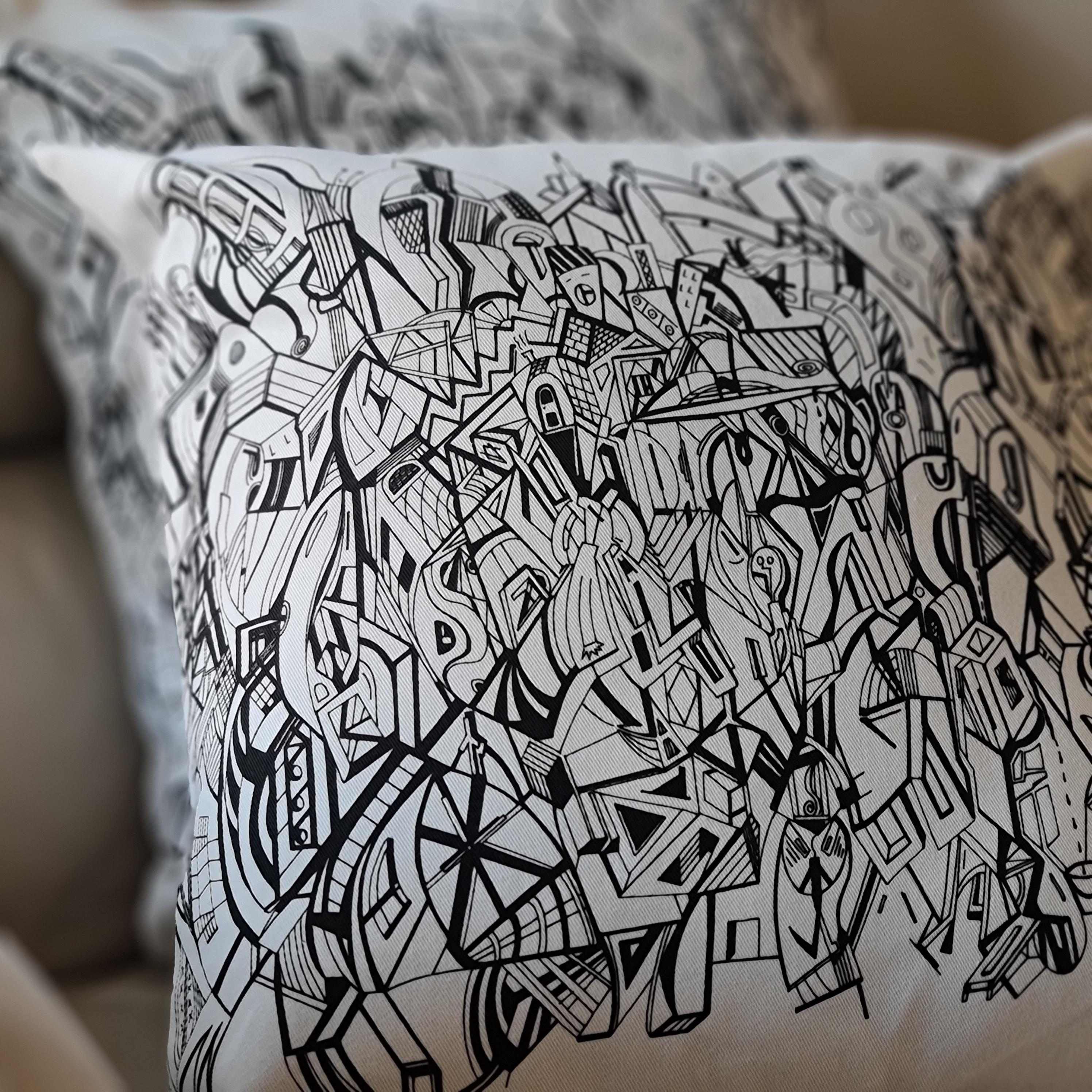 A cream coloured square cushion with the black artwork of Jason Clarke printed on the front