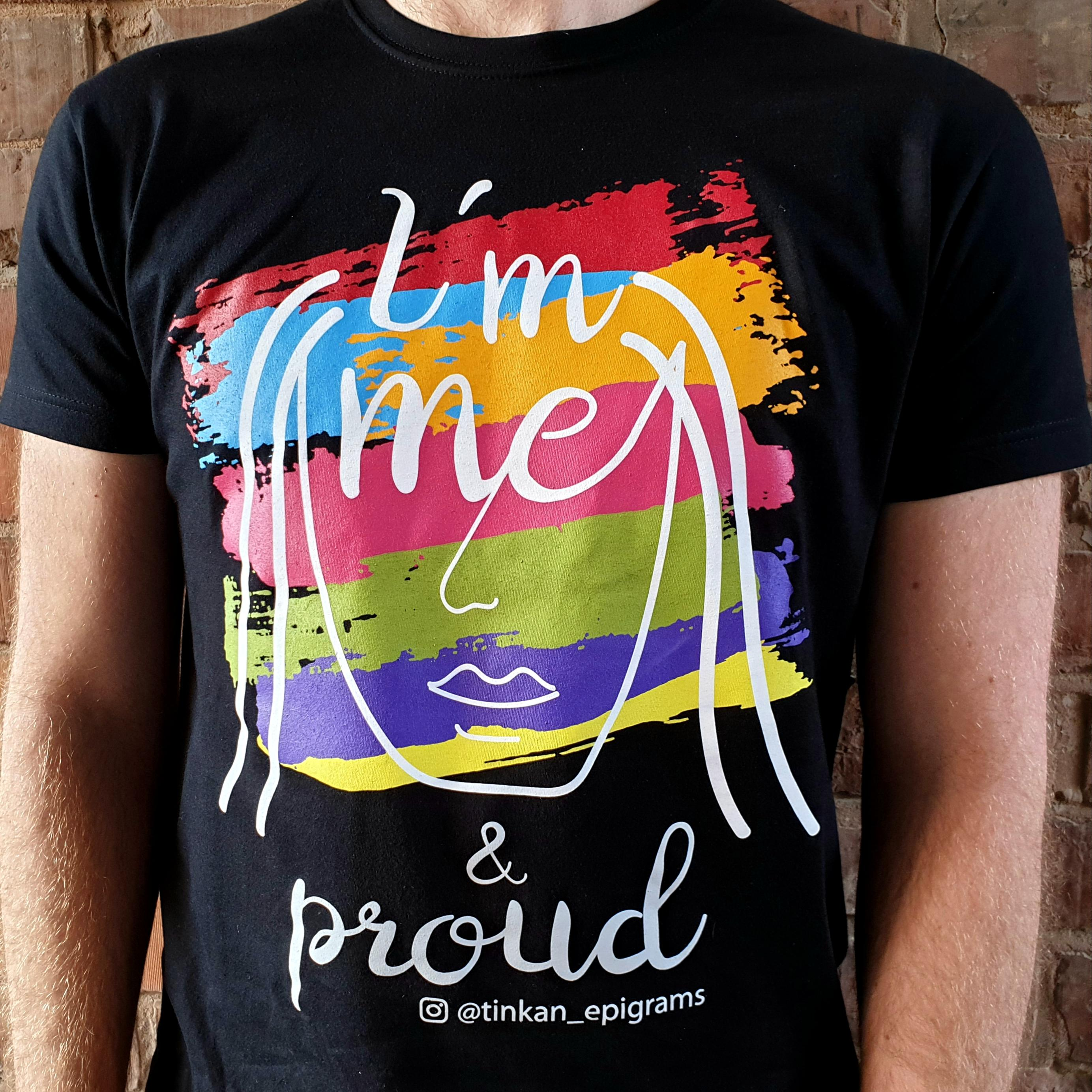 Adult female wearing black t-shirt with white handdrawn face and rainbow painted stripes with the words I'm Me & Proud printed. Designed by thetinkan. VIEW PRODUCT >>